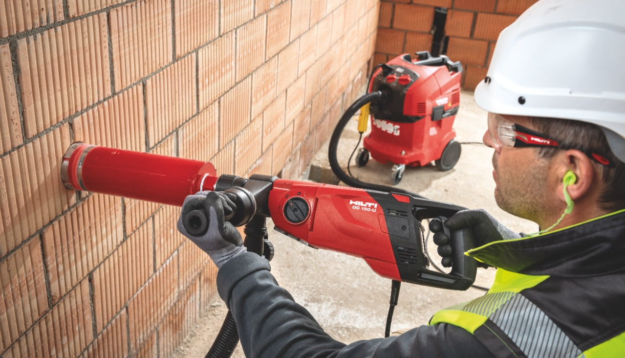Worker performing diamond drilling in brick wall